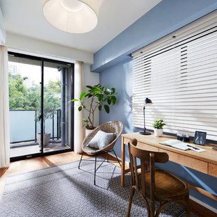東京23区のコンテンポラリースタイルのおしゃれなホームオフィス・書斎 (青い壁、無垢フローリング、自立型机、茶色い床) の写真