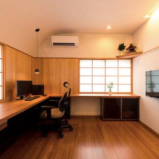 他の地域のモダンスタイルのおしゃれな書斎 (白い壁、無垢フローリング、暖炉なし、造り付け机、茶色い床) の写真