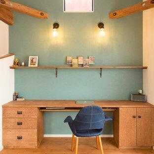 他の地域のアジアンスタイルのおしゃれなホームオフィス・書斎 (青い壁、無垢フローリング、造り付け机、茶色い床) の写真