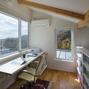 他の地域のモダンスタイルのおしゃれなホームオフィス・書斎 (ライブラリー、白い壁、無垢フローリング、造り付け机、茶色い床) の写真
