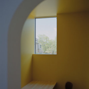 Cette image montre un bureau avec un mur jaune, un sol en contreplaqué, un bureau intégré, un sol marron, un plafond en lambris de bois et du lambris de bois.