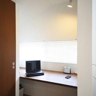 Inspiration pour un petit bureau design avec un mur blanc, un sol en contreplaqué, un bureau intégré et un sol marron.