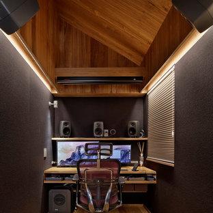 Idee per un piccolo studio moderno con pareti multicolore, pavimento in legno massello medio, scrivania incassata e pavimento marrone