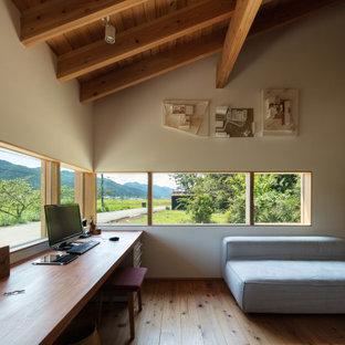 Modelo de despacho madera, asiático, grande, con paredes beige, suelo de madera en tonos medios, escritorio empotrado y suelo beige