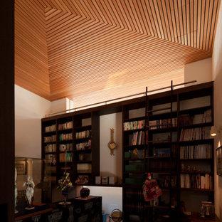 Aménagement d'un bureau moderne de taille moyenne avec un mur blanc, un sol en bois foncé, aucune cheminée, un bureau intégré et un sol marron.