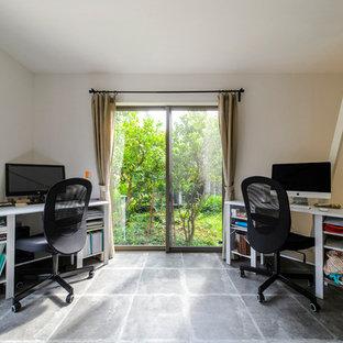 インダストリアルスタイルのおしゃれなホームオフィス・書斎 (白い壁、コンクリートの床、自立型机、グレーの床) の写真