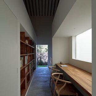 他の地域のコンテンポラリースタイルのおしゃれなホームオフィス・書斎 (白い壁、コンクリートの床、造り付け机、グレーの床) の写真