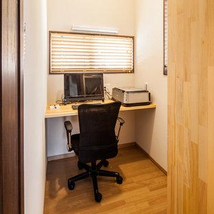 Exemple d'un bureau avec un mur blanc, un sol en contreplaqué, un bureau intégré, un sol marron, un plafond en papier peint et du papier peint.