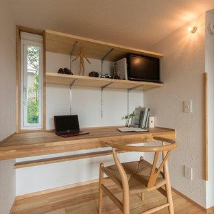 Inspiration för ett litet orientaliskt arbetsrum, med vita väggar, mellanmörkt trägolv, ett inbyggt skrivbord och brunt golv