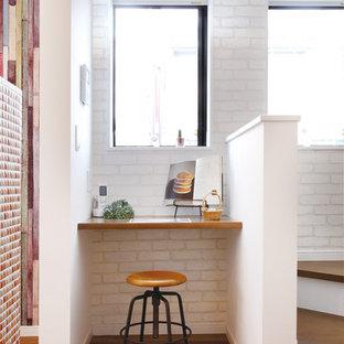 Idee per uno studio moderno con pareti multicolore, pavimento in compensato, scrivania incassata e pavimento marrone