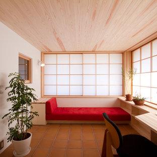 Modelo de despacho de estilo zen con paredes blancas, suelo de baldosas de terracota y escritorio empotrado