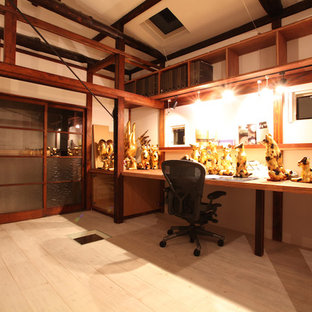 Example of a mid-sized built-in desk light wood floor home studio design in Tokyo with white walls and no fireplace