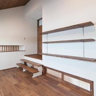 Immagine di un piccolo studio etnico con libreria, pareti bianche, pavimento in compensato, scrivania incassata e pavimento marrone