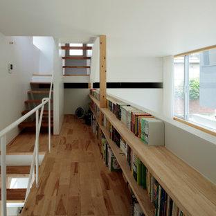 Modern inredning av ett mellanstort arbetsrum, med vita väggar, mellanmörkt trägolv, ett inbyggt skrivbord och brunt golv