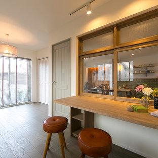 Пример оригинального дизайна: маленькое рабочее место в стиле кантри с белыми стенами, встроенным рабочим столом, коричневым полом, паркетным полом среднего тона и потолком с обоями без камина