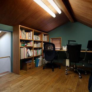 東京都下のコンテンポラリースタイルのおしゃれなホームオフィス・書斎 (緑の壁、無垢フローリング、造り付け机、茶色い床) の写真