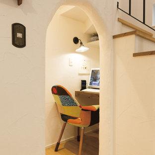 他の地域の小さい地中海スタイルのおしゃれなホームオフィス・書斎 (白い壁、淡色無垢フローリング、造り付け机、ベージュの床) の写真