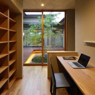 他の地域のアジアンスタイルのおしゃれなホームオフィス・書斎 (茶色い壁、無垢フローリング、造り付け机、茶色い床) の写真
