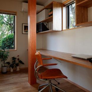 東京23区のアジアンスタイルのおしゃれなホームオフィス・仕事部屋 (白い壁、無垢フローリング、造り付け机、茶色い床) の写真
