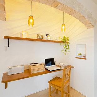 他の地域のカントリー風おしゃれなホームオフィス・仕事部屋 (白い壁、淡色無垢フローリング、造り付け机、茶色い床) の写真