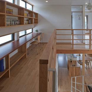 Diseño de despacho asiático, sin chimenea, con paredes blancas, suelo de madera clara, escritorio empotrado y suelo beige