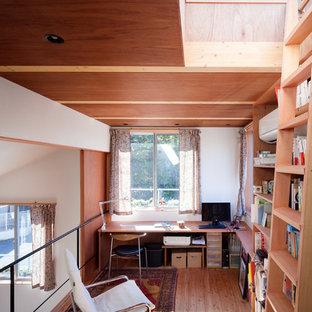 中くらいのモダンスタイルのおしゃれなホームオフィス・書斎 (ライブラリー、白い壁、無垢フローリング、暖炉なし、造り付け机、茶色い床) の写真