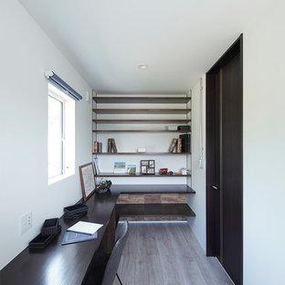 他の地域のモダンスタイルのおしゃれなホームオフィス・書斎 (白い壁、造り付け机、グレーの床) の写真