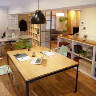 他の地域のインダストリアルスタイルのおしゃれなホームオフィス・仕事部屋 (白い壁、無垢フローリング、自立型机、茶色い床) の写真