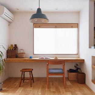 カントリー風おしゃれなホームオフィス・書斎 (白い壁、無垢フローリング、造り付け机、茶色い床) の写真