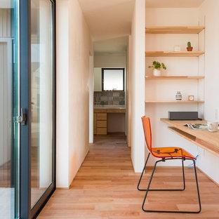 他の地域のモダンスタイルのおしゃれなホームオフィス・書斎 (白い壁、無垢フローリング、造り付け机、茶色い床) の写真