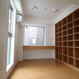 Esempio di un piccolo atelier scandinavo con pareti bianche, pavimento in compensato, nessun camino, scrivania incassata e pavimento marrone