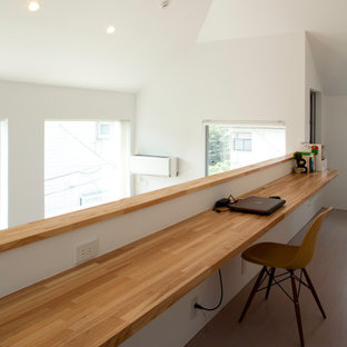 Idéer för att renovera ett mellanstort funkis hobbyrum, med vita väggar, plywoodgolv, ett inbyggt skrivbord och beiget golv