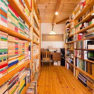 Diseño de despacho asiático con paredes blancas, suelo de madera en tonos medios, escritorio independiente y suelo marrón