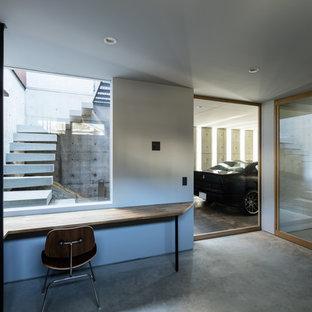 他の地域の大きいモダンスタイルのおしゃれなアトリエ・スタジオ (グレーの壁、コンクリートの床、暖炉なし、造り付け机、グレーの床) の写真