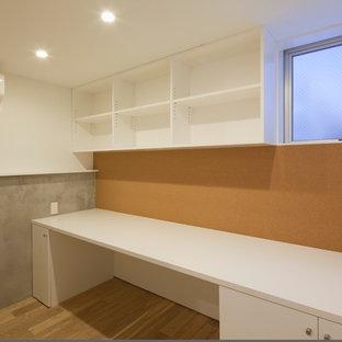 Foto di un atelier moderno con pareti marroni, pavimento in compensato, nessun camino, scrivania incassata e pavimento beige