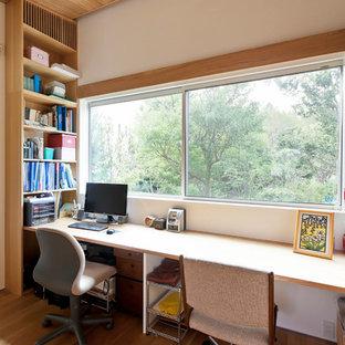 Mittelgroßes Asiatisches Arbeitszimmer mit Arbeitsplatz, weißer Wandfarbe, braunem Holzboden, Einbau-Schreibtisch und braunem Boden in Sonstige