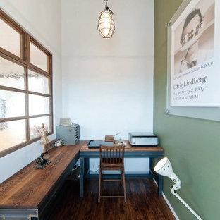 Foto på ett litet industriellt arbetsrum, med gröna väggar, mörkt trägolv och ett fristående skrivbord