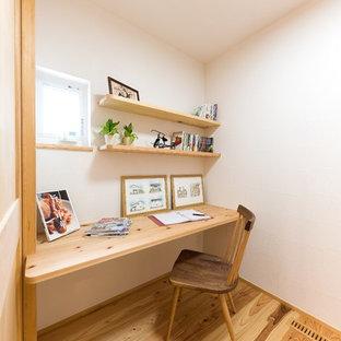 На фото: кабинет в восточном стиле с белыми стенами, паркетным полом среднего тона, встроенным рабочим столом и коричневым полом с