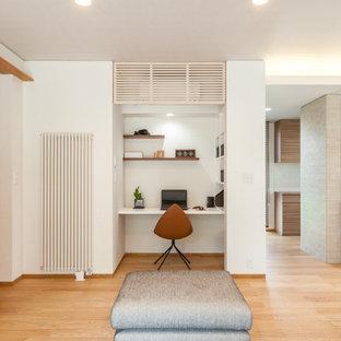 他の地域の小さいモダンスタイルのおしゃれなホームオフィス・仕事部屋 (白い壁、淡色無垢フローリング、造り付け机、茶色い床) の写真