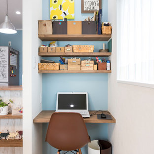 Réalisation d'un petit bureau nordique avec un mur bleu, un sol en bois brun, aucune cheminée et un bureau intégré.