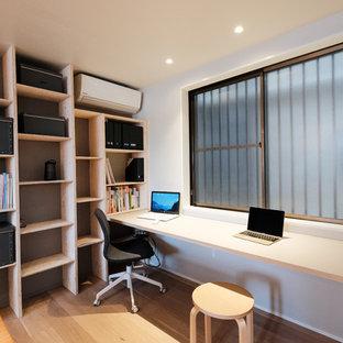 東京23区のインダストリアルスタイルのおしゃれなホームオフィス・仕事部屋 (マルチカラーの壁、淡色無垢フローリング、造り付け机、ベージュの床) の写真