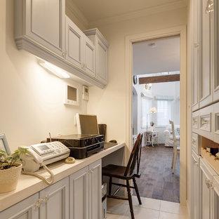 他の地域の小さいトラディショナルスタイルのおしゃれなホームオフィス・仕事部屋 (白い壁、造り付け机、ベージュの床) の写真