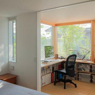 Exemple d'un bureau scandinave de taille moyenne avec un mur blanc, un sol en bois clair, une cheminée standard, un manteau de cheminée en pierre, un bureau intégré et un sol beige.