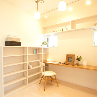 Пример оригинального дизайна: маленькое рабочее место в скандинавском стиле с белыми стенами, светлым паркетным полом, встроенным рабочим столом и коричневым полом