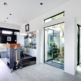東京23区のモダンスタイルのおしゃれなホームオフィス・書斎 (マルチカラーの壁、造り付け机、黒い床) の写真