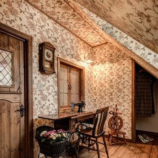 シャビーシック調のおしゃれなホームオフィス・仕事部屋 (マルチカラーの壁、無垢フローリング、自立型机、茶色い床) の写真