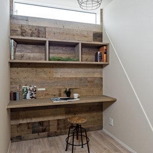 Esempio di un piccolo studio industriale con pareti bianche, pavimento in legno verniciato, scrivania incassata e pavimento grigio