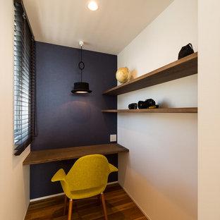 他の地域のコンテンポラリースタイルのおしゃれなホームオフィス・仕事部屋 (マルチカラーの壁、濃色無垢フローリング、造り付け机、茶色い床) の写真