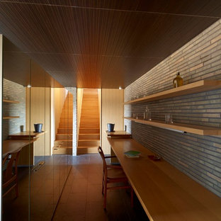 横浜のアジアンスタイルのおしゃれなホームオフィス・書斎 (グレーの壁、造り付け机、茶色い床) の写真