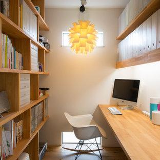 他の地域のコンテンポラリースタイルのおしゃれな書斎 (白い壁、無垢フローリング、造り付け机、茶色い床) の写真